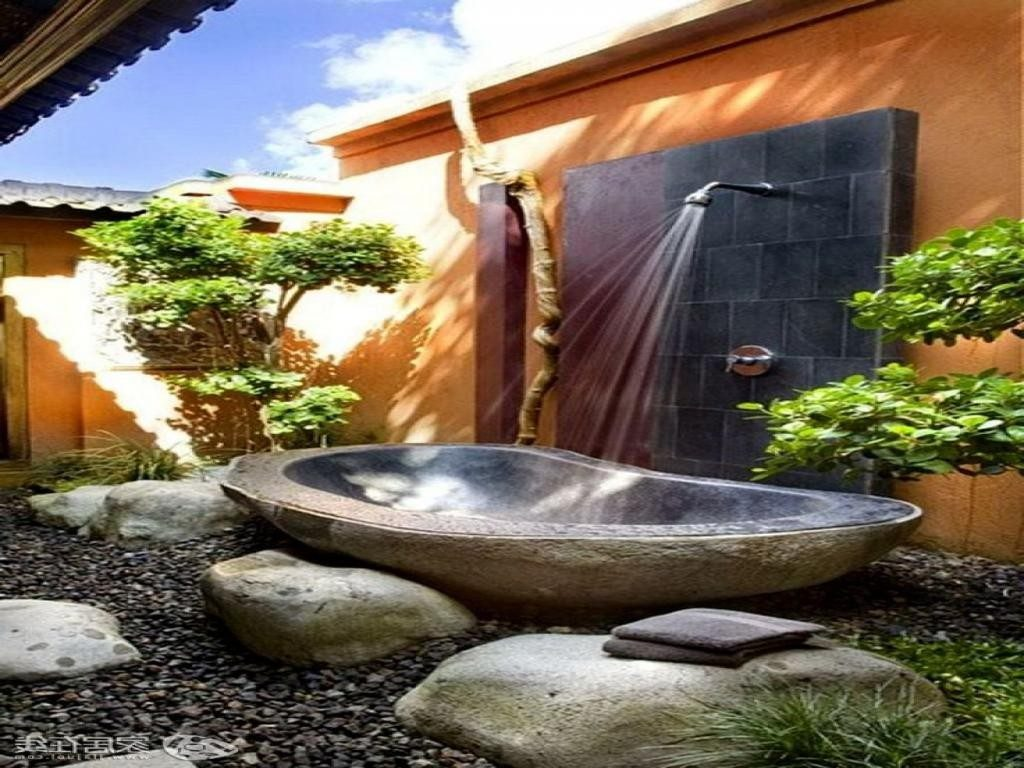 outdoor-nature-bathroom-design-with-shower-above-stone-bathtub-aksi-brown-wall-and-garden-in-the-nearby-1024x768